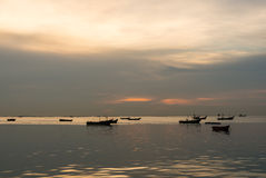 Silhouette of Small fishing boats on the sea during sunset Royalty Free Stock Images