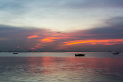 Silhouette of Small fishing boats on the sea during sunset Stock Photos