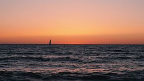 Silhouette of small sailboat in orange dusk. Small boat sailing in sea at sunset. Beautiful calm sea against sunset with sailboat. On horizon. Beautiful sunset stock video