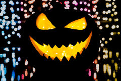 Silhouette of smiling pumpkin on black. With party lights at the background Stock Photos