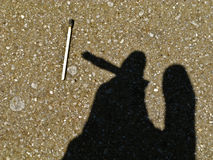 Silhouette of a smoker. Silhouette of a hand holding a cigarette with a burnt match on the ground Stock Photography