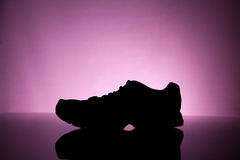 Silhouette of Sneakers. Sport equipment. silhouette of Sneakers on a pink background Stock Photos