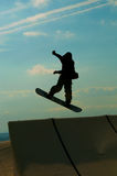 Silhouette the snowboarder jumping high in the blue sky Royalty Free Stock Image