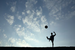 Silhouette of soccer man playing with the ball Stock Photo