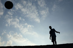 Silhouette of soccer man playing with the ball.  Royalty Free Stock Photo