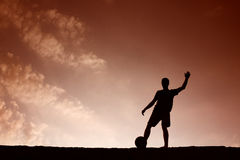 Silhouette of soccer man playing with the ball.  Stock Photos