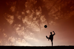 Silhouette of soccer man playing with the ball Royalty Free Stock Photos