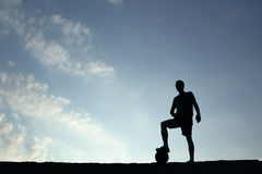 Silhouette of soccer man resting with foot on ball Stock Image