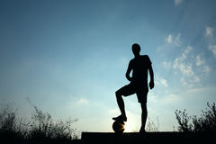 Silhouette of soccer man resting with foot on ball Royalty Free Stock Image