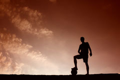 Silhouette of soccer man resting with foot on ball Stock Photography