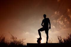 Silhouette of soccer man resting with foot on ball Royalty Free Stock Photography