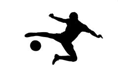 A silhouette of a soccer player shooting a ball Royalty Free Stock Image