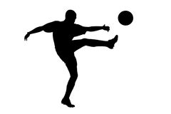 A silhouette of a soccer player shooting a ball Stock Photos