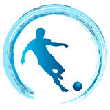 Silhouette of soccer player striking the ball Stock Image