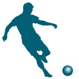 Silhouette of soccer player striking the ball Royalty Free Stock Images
