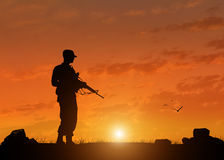 Silhouette of soldier with a gun Stock Images