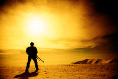 Silhouette of soldier with sniper rifle. Standing under scorching sun in the mountains Stock Images