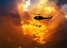 Silhouette soldiers in action rappelling climb down from helicopter with military mission counter terrorism assault training Royalty Free Stock Image
