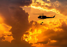 Silhouette soldiers in action rappelling climb down from helicopter with military mission counter terrorism assault training on su Royalty Free Stock Photos