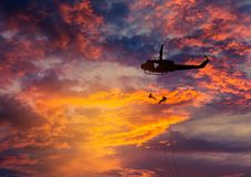 Silhouette soldiers in rappelling climb down from helicopter with military mission counter terrorism assault training on su Stock Image