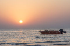 Silhouette of speed boat with sunset. At beach Royalty Free Stock Photography