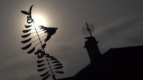 Silhouette of spinning weather vane in the backyard at sunset. Silhouette of modern weather vane at sunset spinning at gentle breeze stock footage