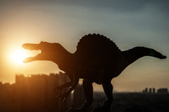 Silhouette of spinosaurus and buildings in a sunset time Stock Photos