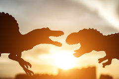 Silhouette of spinosaurus and tyrannosaurus with buildings in far end in sunset. Time Stock Images