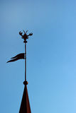 Silhouette of spire topped with flag and crab shaped weathercock.  Stock Images