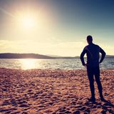 Silhouette of sport active adult man running and exercising on the beach. Calm water Stock Photos