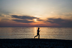 Silhouette of sport active man running and exercising on the beach at sunset Royalty Free Stock Photography