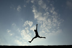 Silhouette of sport man jumping with blue sky and clouds on back Stock Photography
