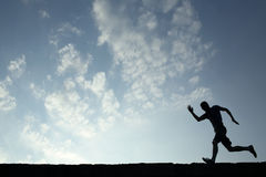 Silhouette of sport man running with blue sky and clouds on back Royalty Free Stock Images