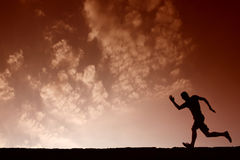 Silhouette of sport man running with blue sky and clouds on back Royalty Free Stock Photography