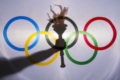 Silhouette of Sport Torch Behind Olympic Flag Stock Image