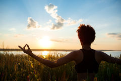 Silhouette of sportive girl practicing yoga in field at sunrise. Royalty Free Stock Image