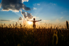 Silhouette of sportive girl practicing yoga in field at sunrise. Royalty Free Stock Photo