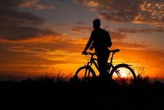 Silhouette of sports person cycling on the meadow. On the beautiful sunset. Young man with camera and bicycle royalty free stock photography