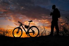 Silhouette of sports person cycling on the meadow. On the beautiful sunset. Young man with camera and bicycle royalty free stock photo
