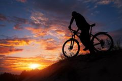Silhouette of sports person cycling on the meadow. On the beautiful sunset. Young man riding bicycle royalty free stock photos