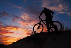 Silhouette of sports person cycling on the meadow royalty free stock photos