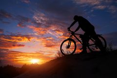 Silhouette of sports person cycling on the meadow. On the beautiful sunset. Young man riding bicycle stock photos
