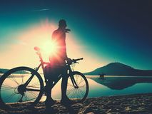 Silhouette of sportsman  holding bicycle on lake beach, colorful  sunset cloudy sky in background. And reflection in smooth water level Stock Photos