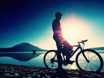 Silhouette of sportsman  holding bicycle on lake beach, colorful  sunset cloudy sky in background. And reflection in smooth water level Stock Image