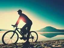 Silhouette of sportsman  holding bicycle on lake beach, colorful  sunset cloudy sky in background. And reflection in smooth water level Stock Photography