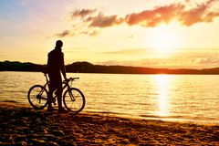 Silhouette of sportsman  holding bicycle on lake bech, colorful  sunset cloudy sky and reflection in wavy water level Royalty Free Stock Photos