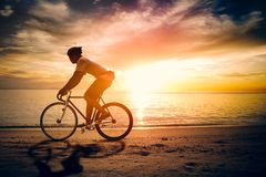 Silhouette of sportsman ride bicycle stock photo