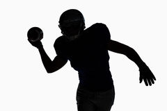 Silhouette sportsman throwing football Stock Image