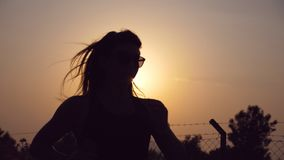 Silhouette of sporty girl jogging in country road at sunset and listening music. Young woman in sunglasses running. Outdoors at sunset. Healthy active lifestyle stock footage