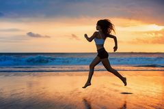 Silhouette of sporty girl running by beach sea surf pool. Barefoot sporty girl silhouette running along ocean surf by water pool to keep fit and health. Sunset Stock Photo